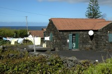 An unpainted house of black volcanic rock, on the North coast
