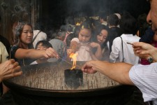 People lighting up some incense sticks in front of a temple