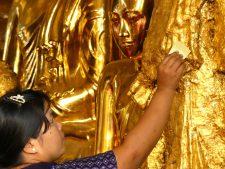 Ritual gold leaf appllication on a Buddha image of Shwedagon Pagoda in Yangon